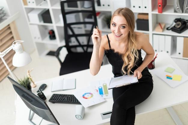 Una joven se sienta en una mesa en la oficina y sostiene un bolígrafo y una tableta con sábanas.