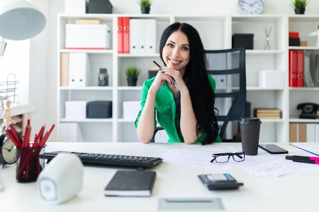 Una joven se sienta en la mesa de la oficina y sostiene un lápiz en sus manos.