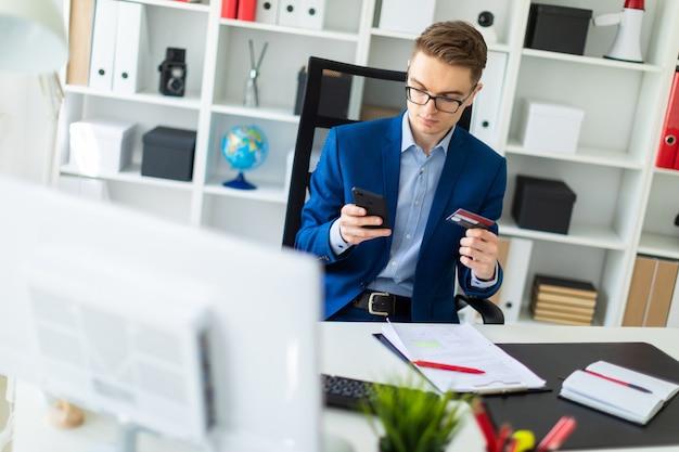 Un joven se sienta en una mesa en la oficina y sostiene una tarjeta bancaria y un teléfono.