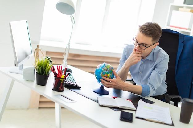 Un joven se sienta en la oficina frente al escritorio de una computadora, mira el globo y piensa.