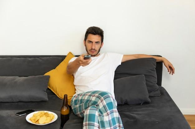 Un joven se sienta en su casa en el sofá y ve la televisión solo. bebe cerveza y come papas fritas.