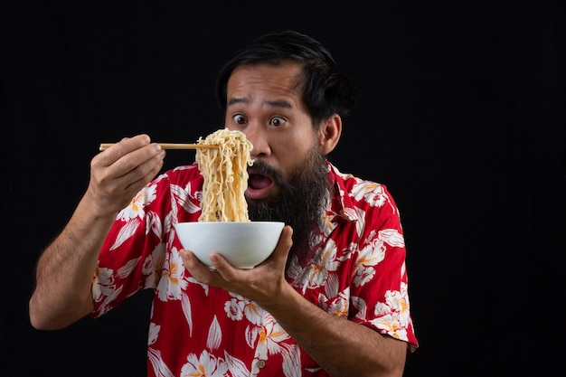 El joven se siente sorprendido con lo deliciosos que son los fideos instantáneos. joven es disfrutar eatting fideos instantáneos en casa.