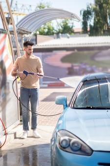 Joven sirviendo su automóvil en el lavado de autos