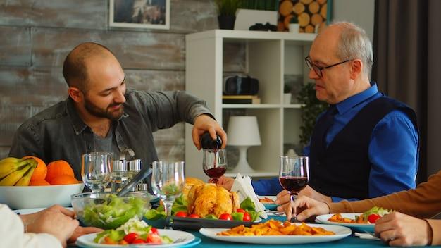 Joven sirviendo a su suegro con vino tinto en el almuerzo familiar. comida deliciosa.