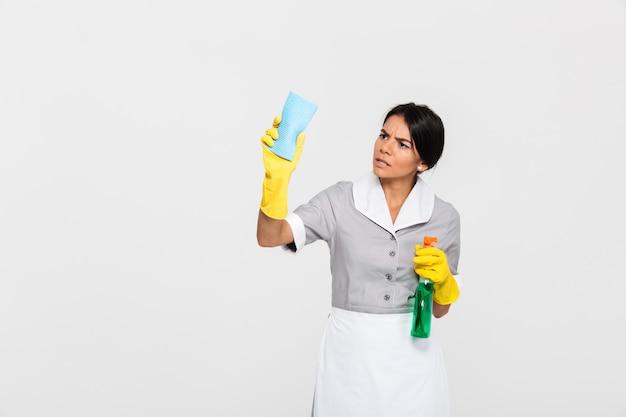 Joven sirvienta concentrada en uniforme de limpieza de ventanas con un trapo