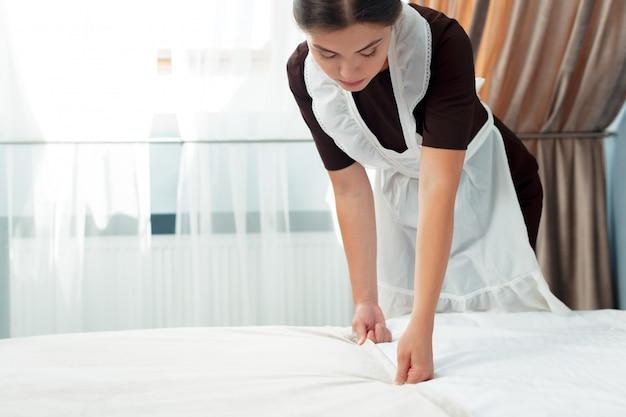 Joven sirvienta haciendo cama en la habitación del hotel