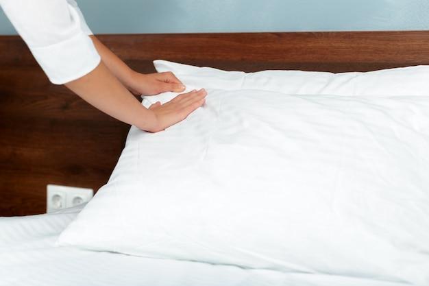 Joven sirvienta haciendo cama en habitación de hotel.