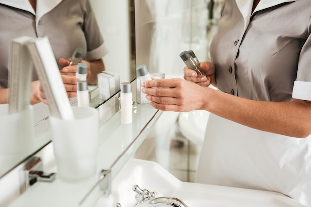 Joven sirvienta del hotel poniendo accesorios de baño en un baño