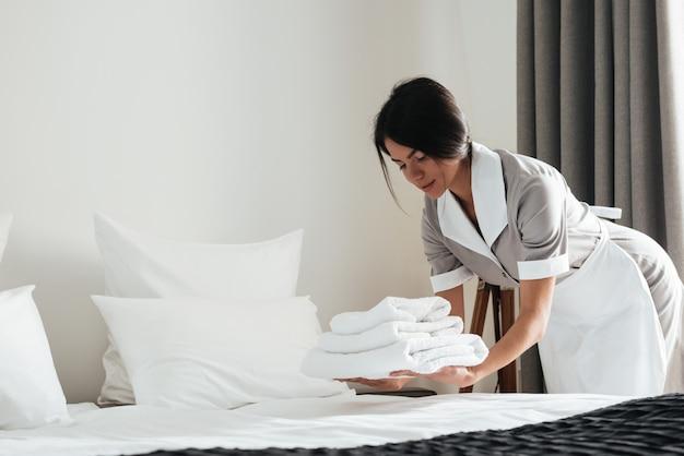 Joven sirvienta del hotel poniendo pila de toallas de baño blancas frescas