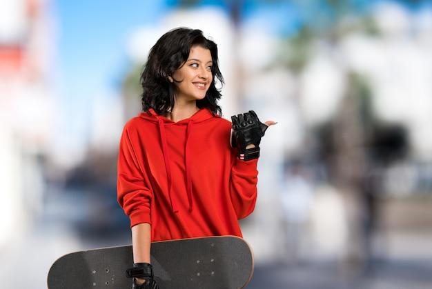 Joven skater mujer apuntando hacia un lado para presentar un producto al aire libre