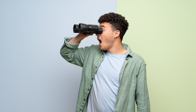 Joven sobre azul y verde y mirando a lo lejos con binoculares