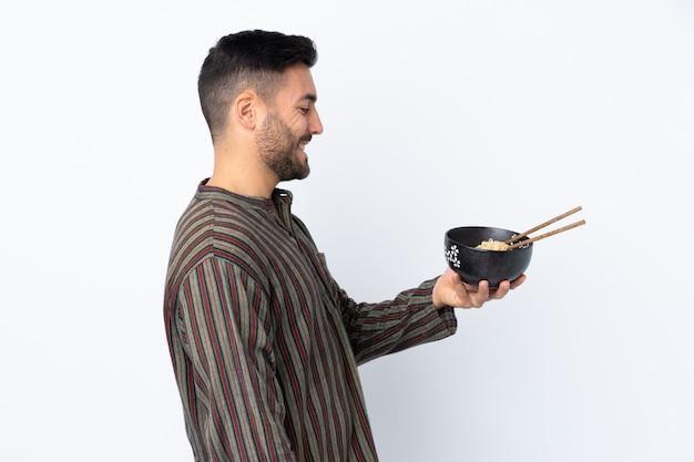 Joven sobre pared aislada con expresión feliz mientras sostiene un tazón de fideos con palillos