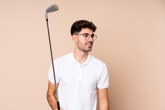 Joven sobre pared aislada jugando al golf