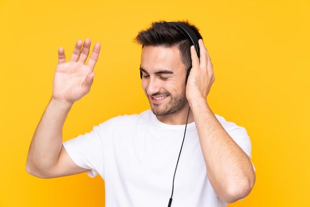 Joven sobre pared amarilla escuchando música y bailando