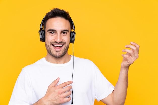 Joven sobre pared amarilla escuchando música y haciendo gesto de guitarra