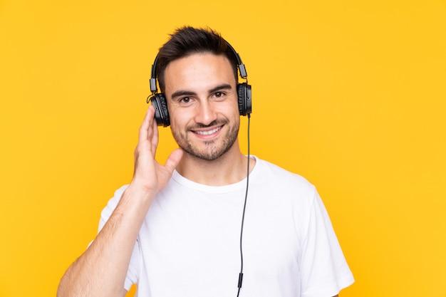 Joven sobre pared amarilla escuchando música