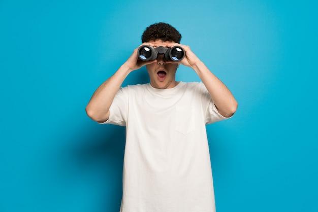 Joven sobre pared azul y mirando a lo lejos con binoculares