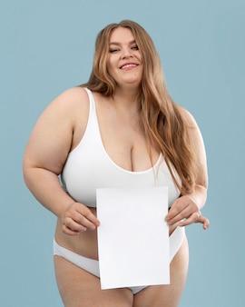 Joven sobredimensionada posando en lencería blanca