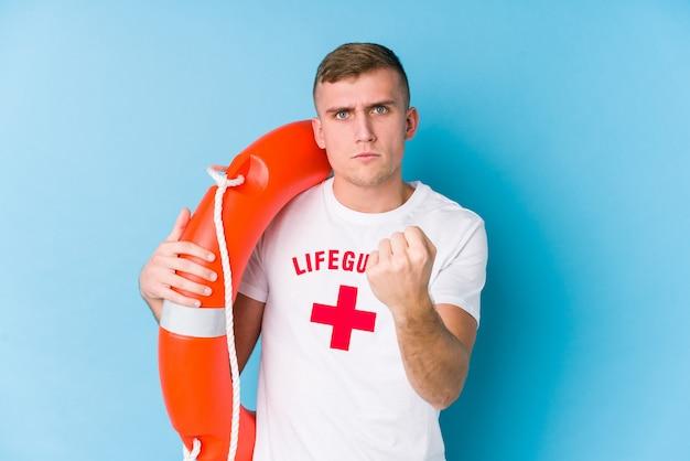Joven socorrista sosteniendo un flotador de rescate mostrando el puño a la cámara, agresiva expresión facial.