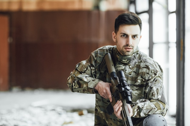 Un joven soldado militar se sienta con un rifle grande en sus manos, cerca de la ventana de un edificio derrumbado.