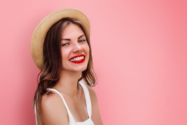 Una joven en sombrero de paja y lápiz labial rojo sonriendo en una pared de color rosa. chica turista divirtiéndose. niña feliz mirando a la cámara sonriendo y riendo espacio para texto
