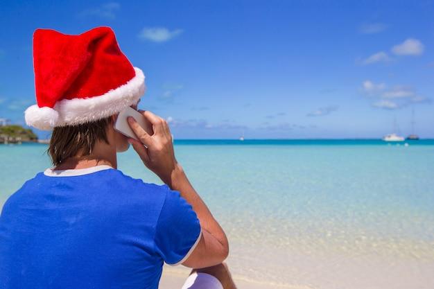 Joven con sombrero de santa hablando por teléfono en la playa tropical