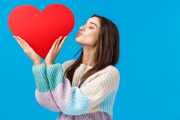 La joven soñadora aprecia su relación, prepara el regalo del día de san valentín, besa un gran letrero rojo lindo sobre el espacio de la copia del lado izquierdo, de pie azul encantado y optimista