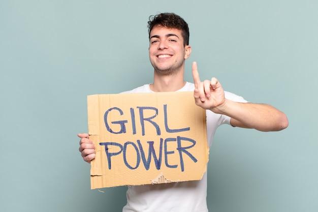 Joven sonriendo con orgullo y confianza haciendo la pose número uno sintiéndose triunfalmente como un líder
