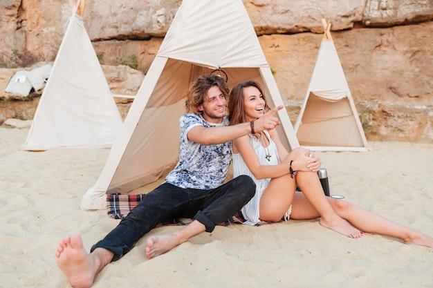 Joven sonriente apuntando con el dedo a algo mientras está sentado en la playa con su novia