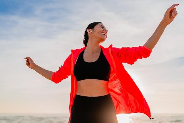 Joven sonriente atractiva mujer delgada haciendo deporte en el amanecer de la mañana bailando en la playa del mar en ropa deportiva, estilo de vida saludable, escuchando música en auriculares, vistiendo chaqueta cortavientos rosa, divirtiéndose