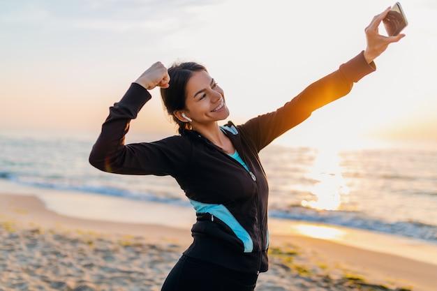Joven sonriente atractiva mujer delgada haciendo ejercicios deportivos en la playa del amanecer de la mañana en ropa deportiva, estilo de vida saludable, escuchando música en auriculares, haciendo que la foto selfie en el teléfono se vea fuerte