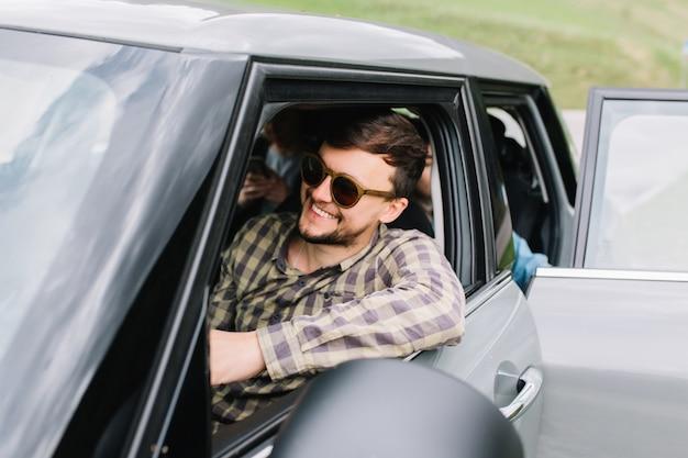Joven sonriente con barba y corte de pelo de moda viajando con la familia por italia en coche