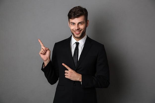Joven sonriente barbudo hombre de negocios apuntando con dos dedos hacia arriba