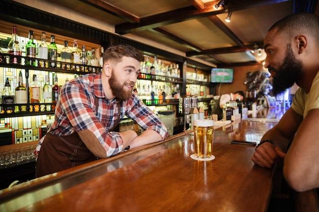Joven sonriente bebiendo cerveza y hablando con el barman en el pub
