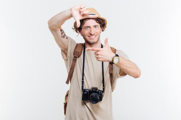 Joven sonriente con cámara retro haciendo gesto fotográfico con las manos aislado sobre un fondo blanco.