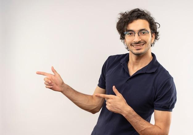 Joven sonriente en camisa negra con gafas ópticas apunta al lado y parece aislado en la pared blanca