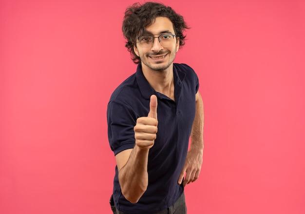 Joven sonriente en camisa negra con gafas ópticas thumbs up y parece aislado en la pared rosa
