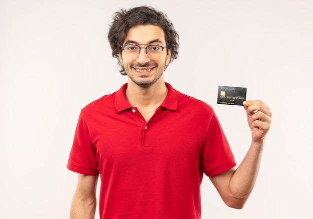 Joven sonriente en camisa roja con gafas ópticas tiene tarjeta de crédito y parece aislado en la pared blanca