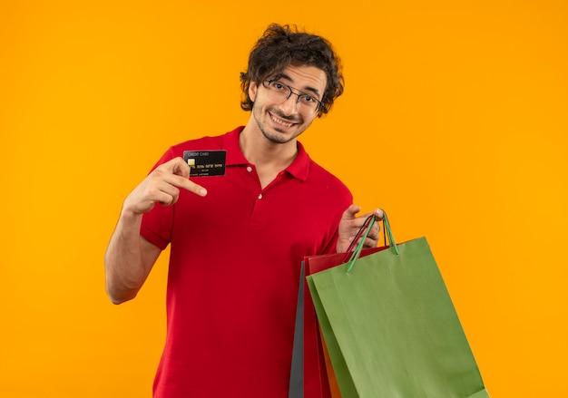 Joven sonriente en camisa roja con gafas ópticas tiene tarjetas de crédito y bolsas de papel aisladas en la pared naranja