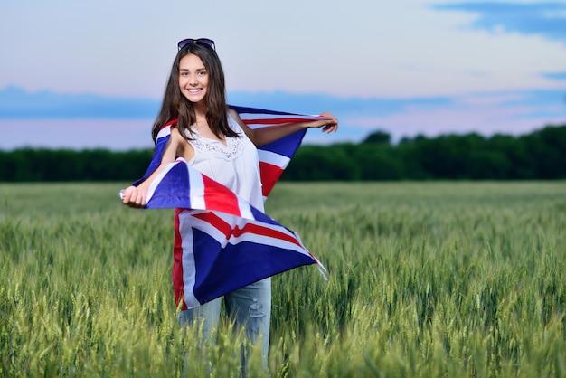 Joven sonriente en un campo de trigo. bandera de la gran bretaña. el concepto de aprender inglés.