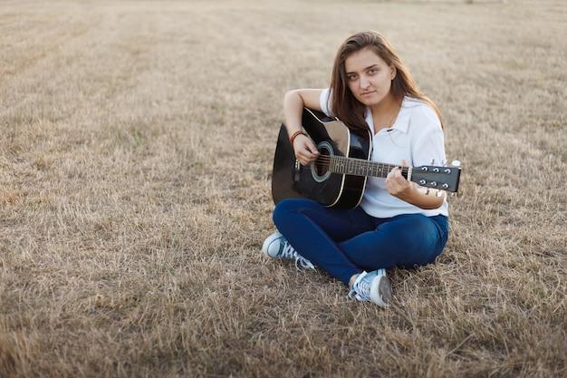 Joven sonriente cantando en la guitarra