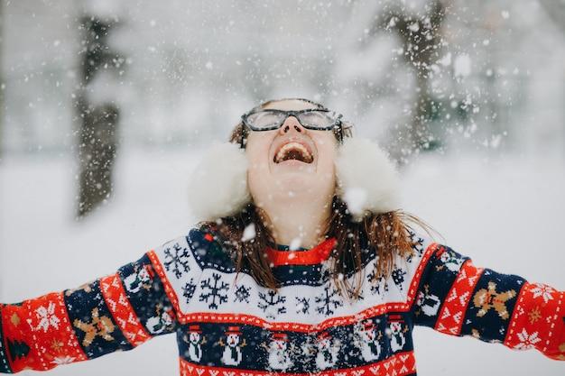 Joven sonriente en chaqueta de invierno lanzando copos de nieve. mujer feliz en el hermoso bosque de pinos en la cima de la montaña rociando nieve en el aire