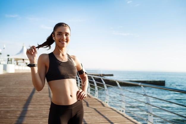Joven sonriente chica fitness lista para ejercicios deportivos junto al mar