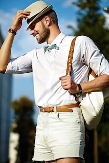 Joven sonriente elegante sexy hombre guapo modelo turístico en estilo de vida casual de tela en la calle con sombrero con bolsa