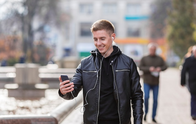 Joven sonriente escuchando música con auriculares afuera