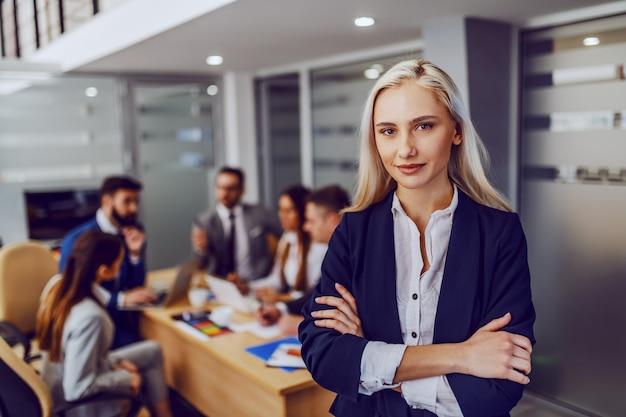 Joven sonriente exitosa empresaria rubia hermosa en ropa formal de pie en la sala de juntas con los brazos cruzados y mirando a la cámara. en segundo plano, sus colegas que tienen reunión.
