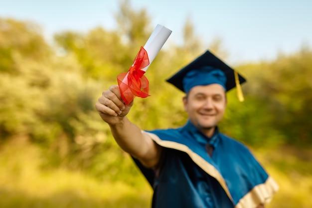 Un joven sonriente feliz celebra su título y su diploma de doctorado. celebrando el concepto de graduación