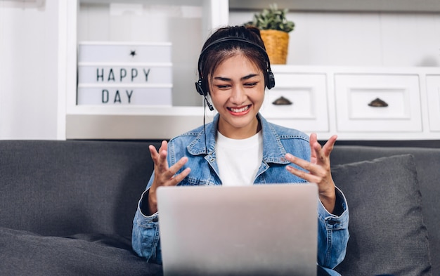 Joven sonriente feliz hermosa mujer asiática relajante utilizando equipo portátil de trabajo y reunión de video conferencia en casa. charla creativa joven con auriculares. trabajar desde casa concepto