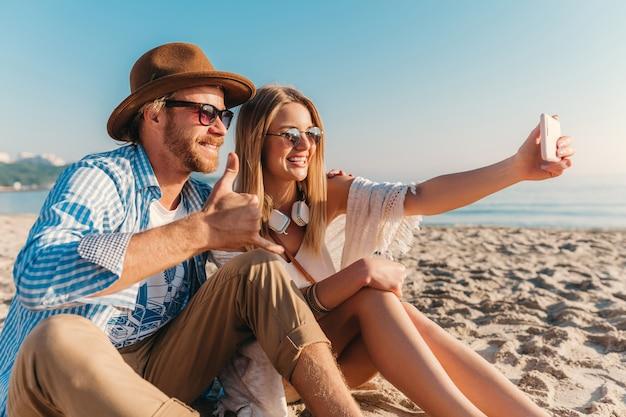 Joven sonriente feliz hombre y mujer en gafas de sol sentado en la playa de arena tomando fotos selfie en la cámara del teléfono