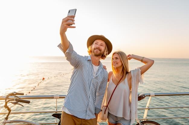 Joven sonriente feliz hombre y mujer viajando en bicicleta tomando selfie foto en la cámara del teléfono